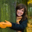 Beautiful romantic woman embracing a tree - golden autumn leaf background — Stock Photo