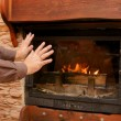 Stock Photo: Man warms up by the fire / fireplace