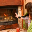 Foto Stock: Womwith daughter warm up by fire / fireplace