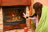 Woman with daughter warm up by the fire / fireplace — Stok fotoğraf
