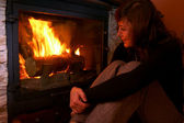 Woman warms up by the fire / fireplace — Stock Photo
