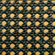 Close-up of green woven rattan pattern over orange - Stock Photo
