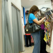 Two women shopping clothes in shop - Stock Photo
