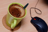 Cup of coffee and mouse on wooden desk — Stock Photo