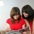 Foto de Stock  : Young two women in reading magazine. Reading at home
