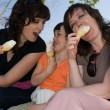 Two women and little girl eating ice-cream - vanilla ice cream. Outdoor — Stock Photo