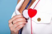 Woman in nurse suit with stetoscope red heart — Stock Photo