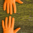 Two hands in gloves on a wooden background — Stock Photo #13822668