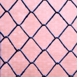 Blue wire fence on pink background - Stock Photo