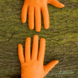 Two hands in gloves on a wooden background — Stock Photo #14038959