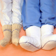 Two Couple's feet warming at a bed — Stock Photo #14039979