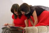 若い 2 人の女性雑誌の読書。家庭で読書 — ストック写真
