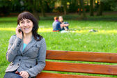 Happy Business woman or student talking on mobile phone in park on bench. — Stock Photo