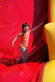 Flicka hoppa på den färgade uppblåsbara bilden — Stockfoto