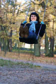 Woman in blue scarf swing on a swing autumn park — Stock Photo
