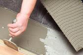Trabajador de la construcción es alicatados en casa piso adhesivo — Foto de Stock