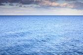 Cloudy blue sky leaving for horizon blue surface sea — Stock Photo