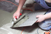 Construction worker is tiling at home tile floor adhesive — Stock Photo