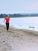 Jonge vrouw wordt uitgevoerd op een strand — Stockfoto