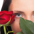 Stock Photo: Closeup portrait of attractive young woman holding a red rose