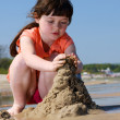 Girl on the beach making sandcastles — Stock Photo #15353901