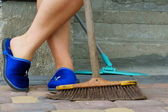 Woman foots and broomstick — Stock Photo