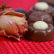 Chocolate pralines candy on red background and rose — Stock Photo