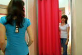 Two women shopping clothes in shop - fitting room — Stock Photo