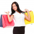 Portrait of young woman carrying shopping bags against white bac - Stock Photo