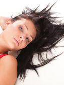 Femme latine en rouge se trouvant sur le blanc de l'étage — Photo