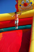 Girl jumping on the colored inflatable slide — Stock Photo
