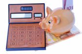 Piggy bank, calculator and euro currency — Stock Photo