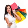 Portrait cute young woman mobile phone while holding shopping bags — Stock Photo #16881179