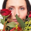 Closeup portrait of attractive young woman holding a red rose — Stock Photo