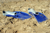 Pair of swimfins on the sand at sea — Stock fotografie