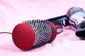 Red round comb and hairdryer on rose background — Stock Photo