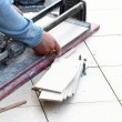 Man cutting tile by cutter - Stock Photo