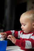 Baby boy playing with bottle and mug indoor — Stock Photo
