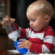 Baby boy playing with bottle and mug indoor — Stock Photo