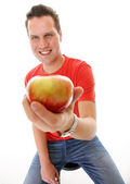 Handsome man in red shirt with apple isolated — Stock Photo