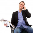 Stock Photo: Young businessmreads newspaper while phoning