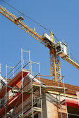 Building tower crane in action against a blue sky — Stock Photo