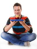 Muž, který držel knihu a jedno červené jablko celého těla — Stock fotografie