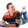 Young man reading a book on the floor isolated - Stock Photo