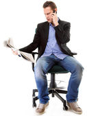 Young businessman reads newspaper while phoning — Stock fotografie