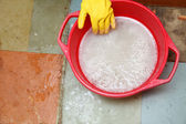 Gloved hand cleaning of dirty filthy floor — Stock Photo