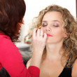 Make up artist applying makeup to a fashion model - Stock Photo