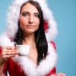 Beautiful girl santa claus Girl blowing hot drink — Stock Photo