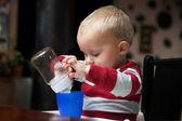 Chłopiec dziecko bawi się butelki i kubek kryty — Zdjęcie stockowe