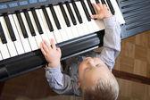 Pouco menino de tocar piano indoor — Fotografia Stock